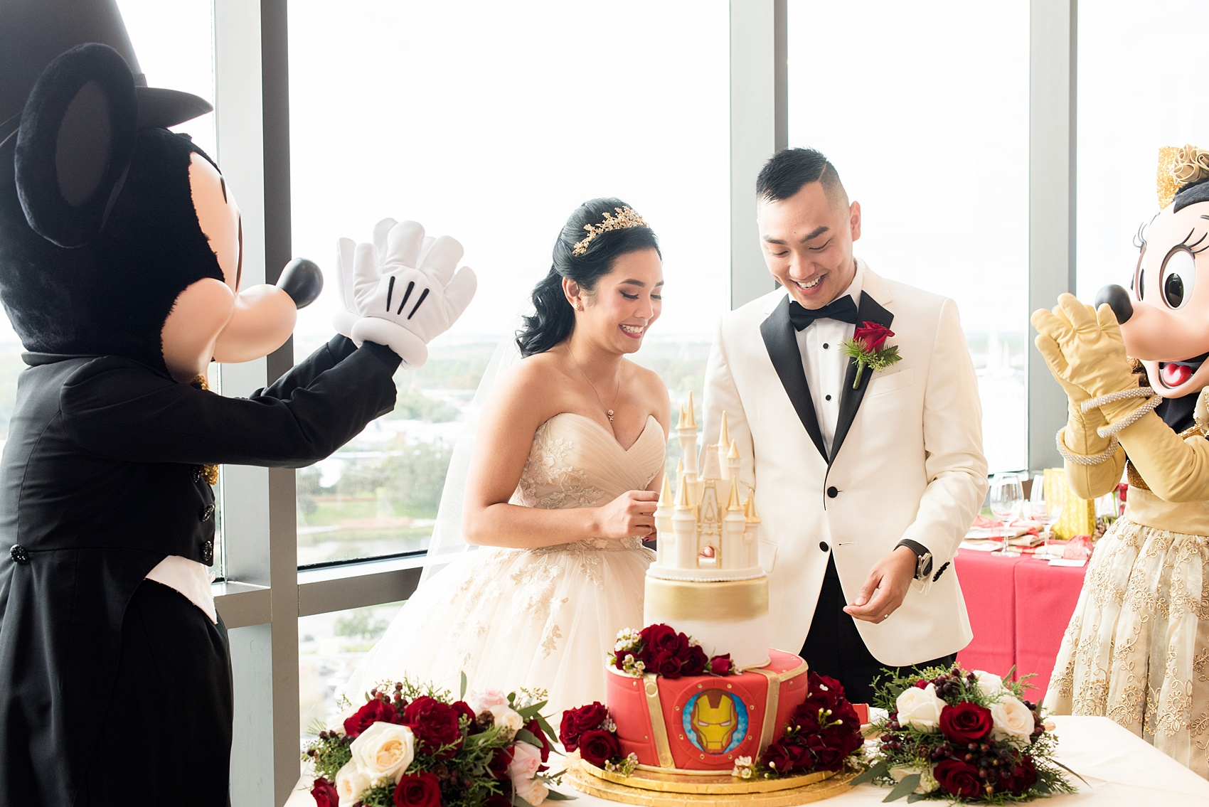 Photographs of a Walt Disney World wedding by Mikkel Paige Photography. The bride and groom had cake cutting help from Mickey Mouse and Minnie Mouse in formal attire! Their reception venue at The Contemporary Resort's California Grill was great for fun, awesome photos with them. It overlooked the Magic Kingdom Park and Cinderella Castle! Their small, dream day included red rose details and a Beauty and the Beast theme. #disneywedding #DisneyWorldWedding #BeautyandtheBeast #MickeyandMinnie