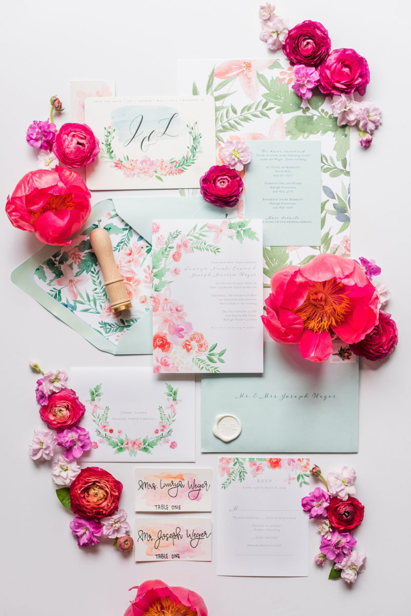 Floral watercolor wedding stationery and invitations for a spring wedding in downtown Raleigh, North Carolina, at the event venue The Stockroom at 230 and The Glass Box. Their photographer, Mikkel Paige Photography, captured this lay flat of their hot pink and aqua blue invitation by @OneandOnlyPaper. #MikkelPaige #DowntownRaleigh #RaleighWedding #RaleighVenue #TheStockroomat230 #floralwatercolorinvitation #weddinginvitation #peonyweddinginspiration #oopaper #oneandonlypaper #layflatphotography