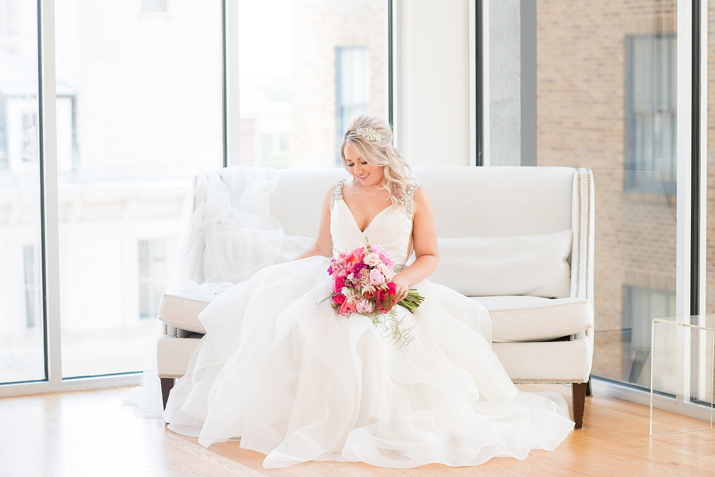 A beautiful spring wedding in Raleigh, North Carolina, at the event venue, The Stockroom at 230 and The Glass Box. Pictures of the bride getting ready with her yorkie dog by their photographer, Mikkel Paige Photography. Their hot pink and aqua colors were perfect for May as the bridesmaids celebrated with a champagne toast in floral robes. #MikkelPaige #DowntownRaleigh #RaleighWedding #RaleighVenue #TheStockroomat230 #bridesmaidsrobes #weddinggettingready