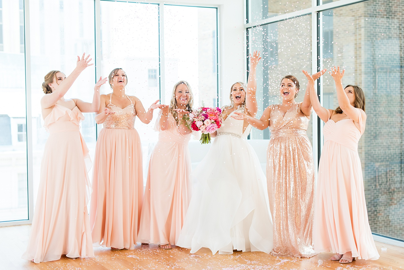 Bridesmaids celebrate with a confetti toss at The Glass Box in downtown Raleigh, North Carolina. The event venue, The Stockroom at 230 was the perfect place for a North Carolina bride and groom to get married. #MikkelPaige #DowntownRaleigh #RaleighWedding #RaleighVenue #TheStockroomat230 #theglassbox #confettiweddingphotos #confetti #weddingparty #bridesmaids