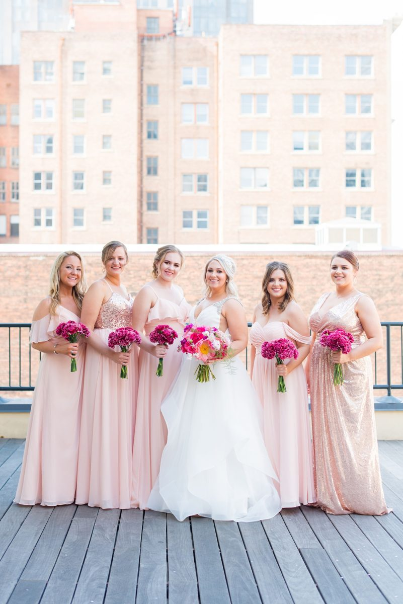 Raleigh wedding photographer, Mikkel Paige Photography, pictures of mismatched pink bridesmaids in downtown Raleigh, North Carolina at the event venue The Stockroom at 230, The Glass Box, and capital building. Their hot pink peony + carnation bouquets were perfect for a spring May celebration. #MikkelPaige #DowntownRaleigh #RaleighWedding #RaleighVenue #TheStockroomat230 #capitalcity #peonies #carnations #pinkbridesmaids #bridalpartyphotos #weddingparty