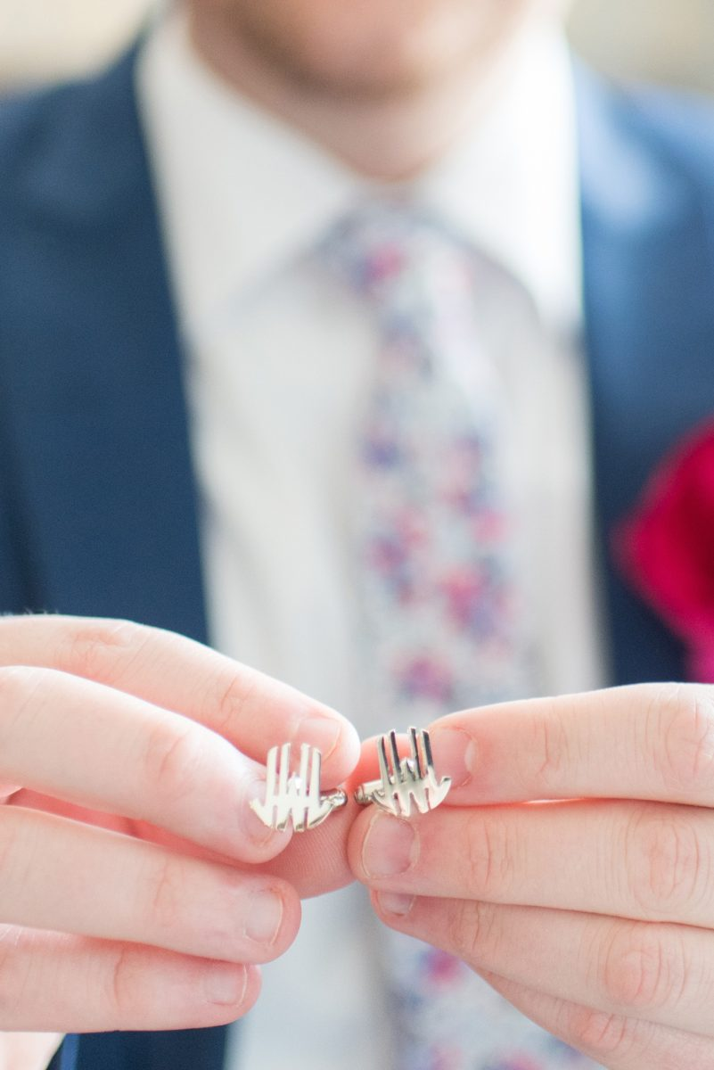 The groom opened a gift from his bride and saw silver custom initial cufflinks for a wedding day gift. Their photographer, Mikkel Paige Photography, captured their spring wedding at the beautiful event venue The Stockroom at 230 in downtown Raleigh, North Carolina. #MikkelPaige #DowntownRaleigh #RaleighWedding #RaleighVenue #TheStockroomat230 #groomgift #customcufflinks #cufflinks #initalcufflinks
