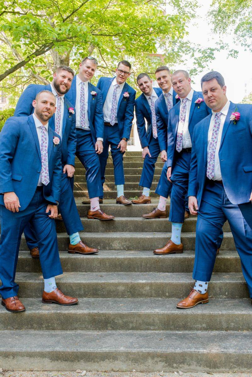 Raleigh wedding photographer, Mikkel Paige Photography, pictures of the groom and his groomsmen in blue suits with floral ties in downtown Raleigh, North Carolina at the event venue The Stockroom at 230 and capital building. The bright colors and hot pink boutonnieres were perfect for a spring May celebration. #MikkelPaige #DowntownRaleigh #RaleighWedding #RaleighVenue #TheStockroomat230 #capitalcity #groomsmen #boutonnieres #bluesuits #floralties #groomstyle