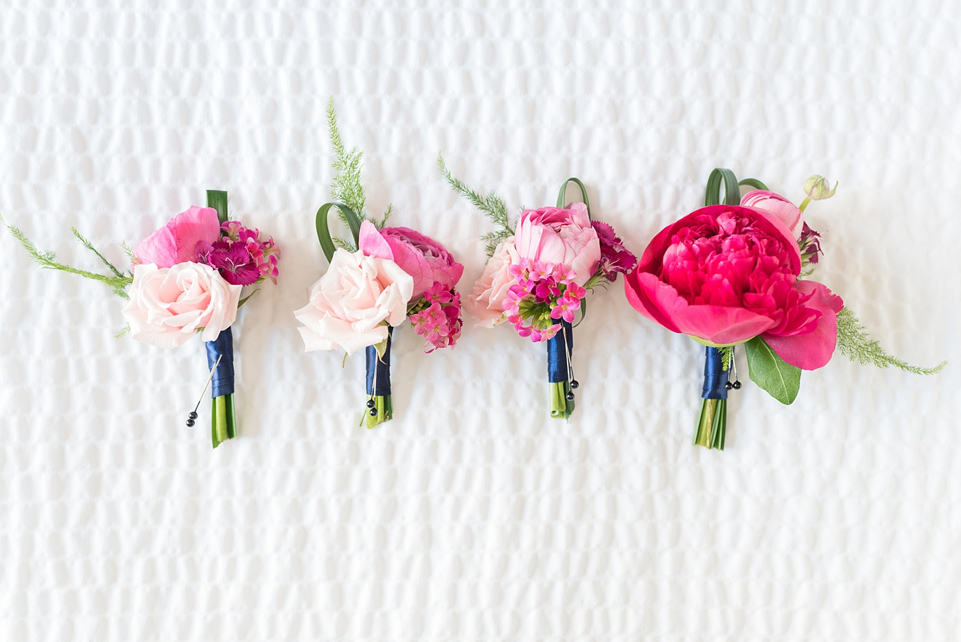Raleigh wedding photographer, Mikkel Paige Photography, pictures of pink boutonnieres by The English Garden Raleigh for a wedding downtown in Raleigh, North Carolina at the event venue The Stockroom at 230. The bright colors and hot pink boutonnieres were perfect for a spring May celebration. #MikkelPaige #DowntownRaleigh #RaleighWedding #RaleighVenue #TheStockroomat230 #capitalcity #groomsmen #boutonnieres #bluesuits #floralties #groomstyle