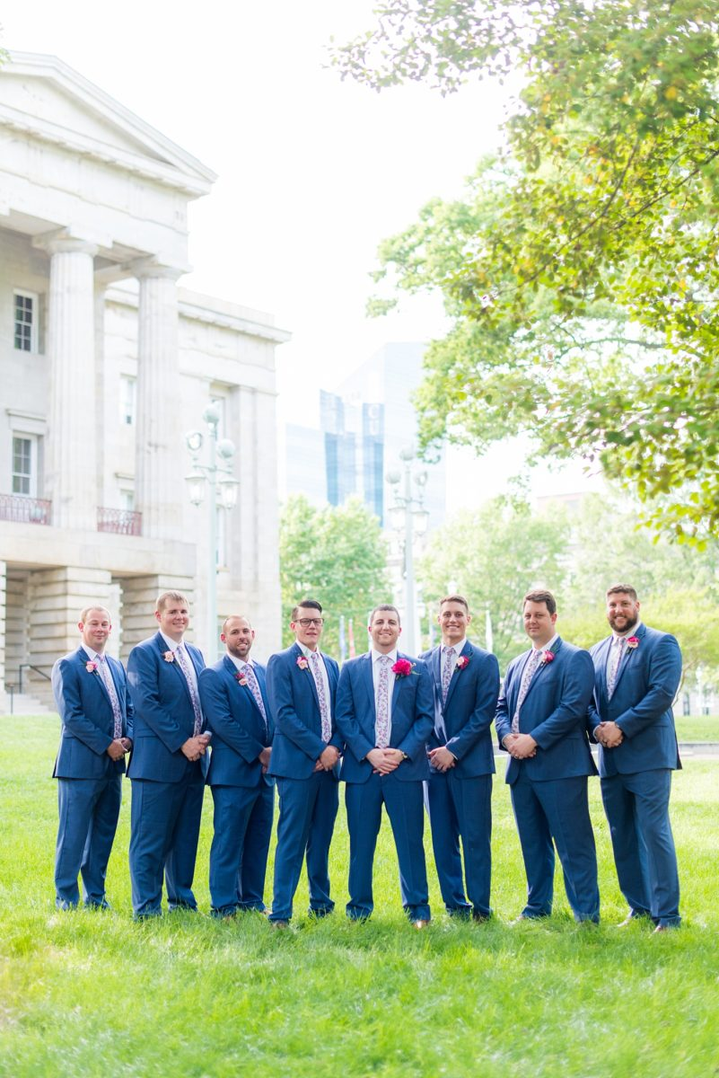 Raleigh wedding photographer, Mikkel Paige Photography, pictures of the groom and his groomsmen in blue suits with floral ties in downtown Raleigh, North Carolina at the event venue The Stockroom at 230 and capital building. The bright colors and hot pink boutonnieres were perfect for a spring May celebration. #MikkelPaige #DowntownRaleigh #RaleighWedding #RaleighVenue #TheStockroomat230 #capitalcity #groomsmen #boutonnieres #bluesuits #floraties #groomstyle #layflatphotography