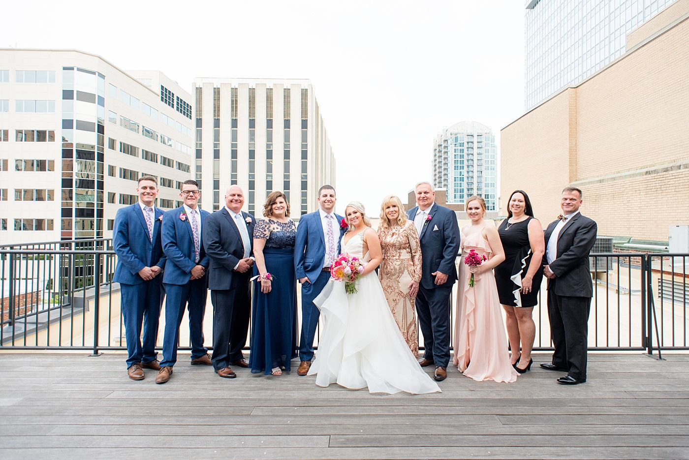 Raleigh wedding photographer, Mikkel Paige Photography, pictures of mismatched pink bridesmaids + groomsmen in blue suits with floral ties in downtown Raleigh, North Carolina at the event venue The Stockroom at 230, The Glass Box, and capital building. Their hot pink peony + carnation bouquets were perfect for a spring May celebration. #MikkelPaige #DowntownRaleigh #RaleighWedding #RaleighVenue #TheStockroomat230 #capitalcity #peonies #carnations #pinkbridesmaids #bridalpartyphotos #weddingparty