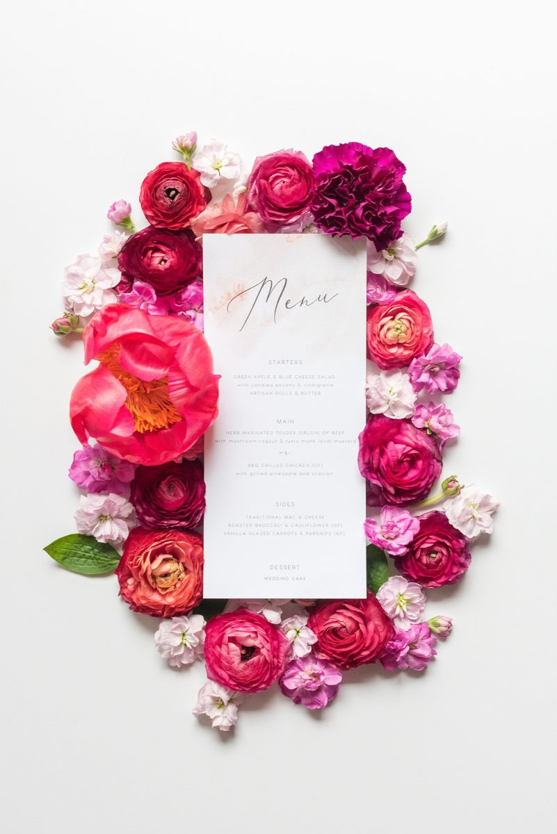 A beautiful spring wedding in downtown Raleigh, North Carolina, at the event venue The Stockroom at 230. Mikkel Paige Photography, their photographer, captured a lay flat of their menu from the reception, with hot pink and aqua blue watercolors and flower detail. #MikkelPaige #DowntownRaleigh #RaleighWedding #RaleighVenue #TheStockroomat230 #weddingreception #weddingmenu #layflatphotography