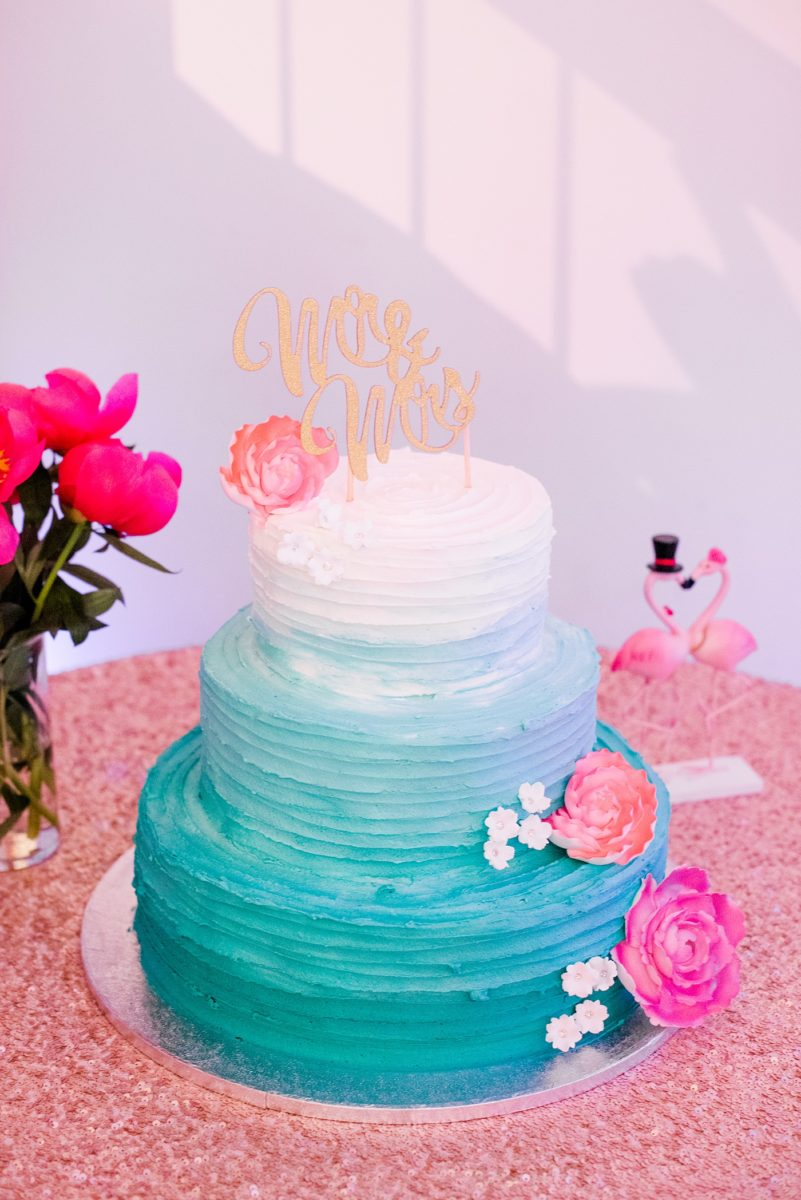"""A spring wedding in downtown Raleigh, North Carolina, at the event venue The Stockroom at 230 with a Publix cake in ombre blue with a """"Mr. and Mrs."""" cake topper and pink flamingos nearby. Mikkel Paige Photography, their photographer, captured a lay flat of their menu from the reception, with hot pink and aqua blue watercolors and flower detail. #MikkelPaige #DowntownRaleigh #RaleighWedding #RaleighVenue #TheStockroomat230 #weddingreception #weddingmenu #weddingcake #ombrecake"""
