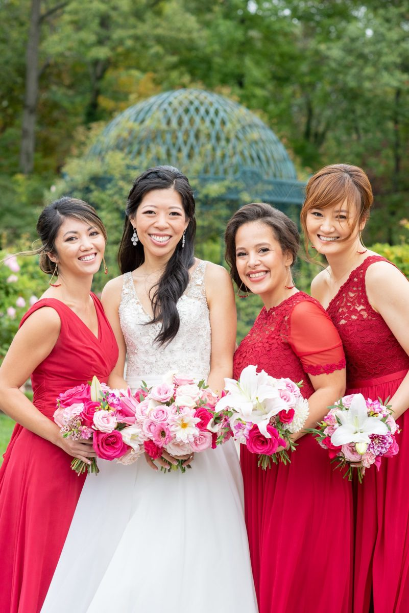 New York Botanical Garden wedding photos with bridesmaids in red gowns and the bride in a beaded bodice and ballgown with long train, by Mikkel Paige Photography. After the couple's engagement photoshoot in Manhattan I was so excited for their fall wedding near the Conservatory at the Terrace Room, at this NYC venue. #mikkelpaige #nybg #newyorkbotanicalgardenwedding #asianbride #NYBotanicalGarden #Bronxwedding #newyorkcityweddingvenues #bridestyle #weddingparty #redbridesmaids #bridalparty