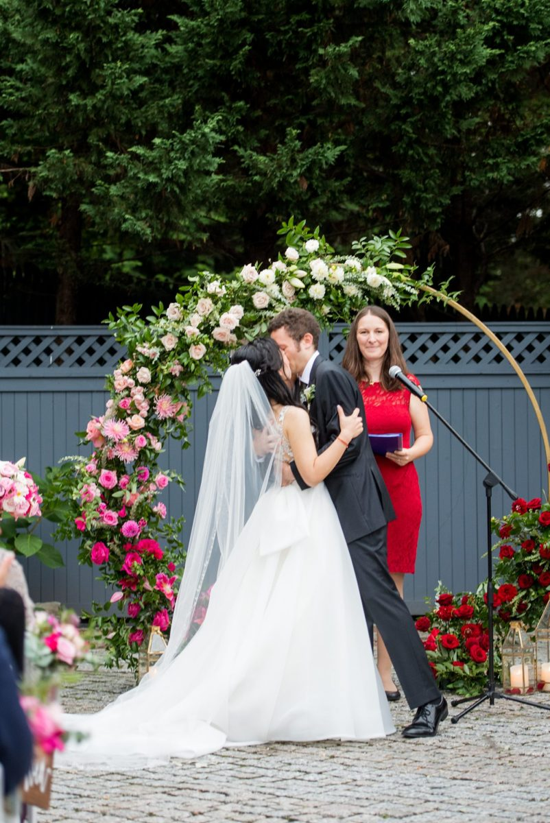 Outdoor ceremony at a New York Botanical Garden wedding photos by Mikkel Paige Photography. After the couple's engagement photoshoot in Manhattan I was so excited for their fall wedding near the Conservatory at the Terrace Room, at this NYC venue. Their backdrop was an ombre flower circle with pink and red blooms. #mikkelpaige #nybg #newyorkbotanicalgardenwedding #asianbride #NYBotanicalGarden #Bronxwedding #newyorkcityweddingvenues #weddingceremony #ombreflowers