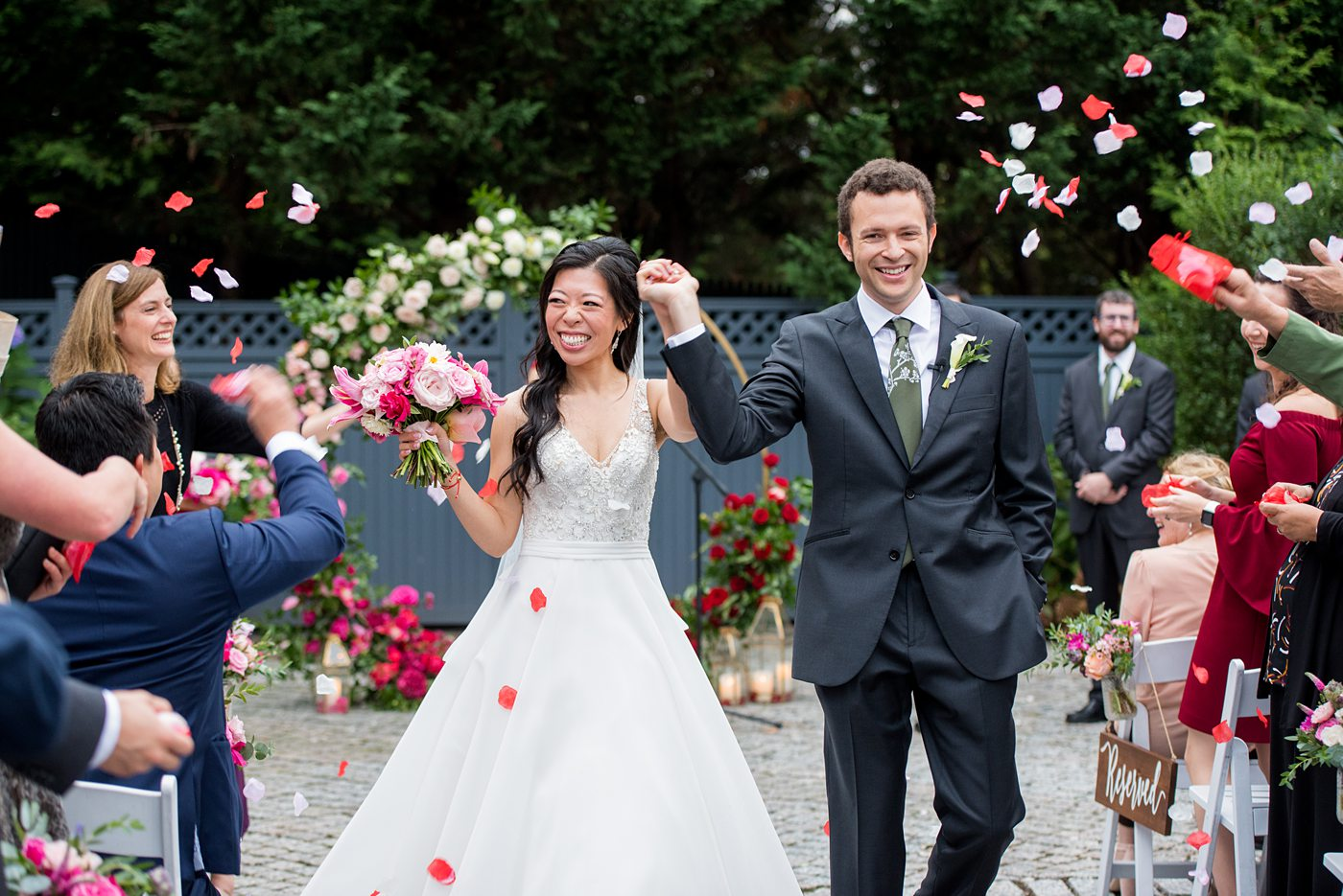 Outdoor ceremony at a New York Botanical Garden wedding photos by Mikkel Paige Photography. After the couple's engagement photoshoot in Manhattan I was so excited for their fall wedding near the Conservatory at the Terrace Room, at this NYC venue. Their backdrop was an ombre flower circle with pink and red blooms. #mikkelpaige #nybg #newyorkbotanicalgardenwedding #asianbride #NYBotanicalGarden #Bronxwedding #newyorkcityweddingvenues #weddingceremony #ombreflowers #tietheknot