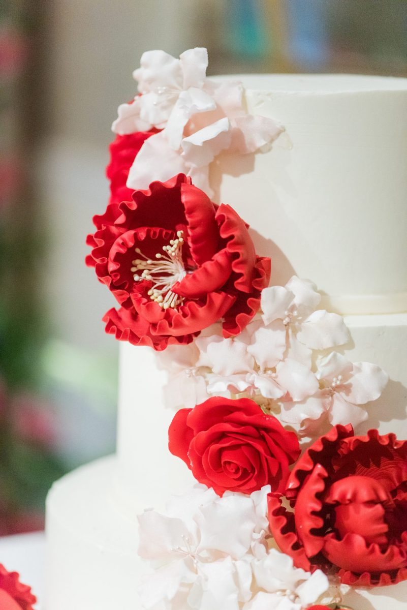 New York Botanical Garden wedding photos by Mikkel Paige Photography with an outdoor ceremony and indoor reception at the Terrace Room. After the couple's engagement photoshoot in Manhattan I was excited for their fall wedding near the Conservatory, at this NYC venue. The bride and groom cut their white fondant cake with red and pink gumpaste flowers. #mikkelpaige #nybg #newyorkbotanicalgardenwedding #NYBotanicalGarden #Bronxwedding #newyorkcityweddingvenues #weddingcake #gumpasteflowers
