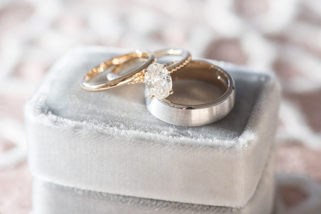 Detail photo of gold diamond rings on a blue velvet ring box at Chatham Station by Mikkel Paige Photography. This beautiful Cary, North Carolina venue has indoor and outdoor spaces. #mikkelpaige #RaleighWeddingPhotographer #NorthCarolinaWeddings #SouthernWeddings #weddingrings #velvetringbox