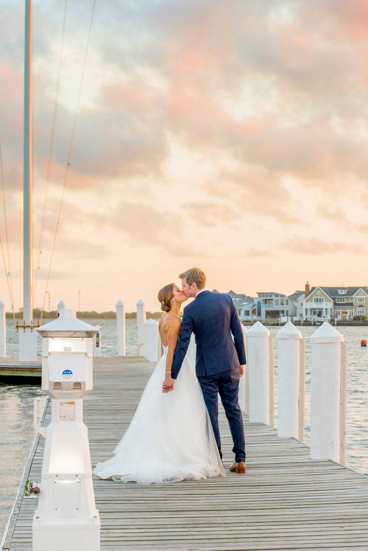 Wedding at Bay Head Yacht Club in New Jersey with picture on the dockside waterfront with the sunset's candy colored pink and blue sky. Pictures by Mikkel Paige Photography.