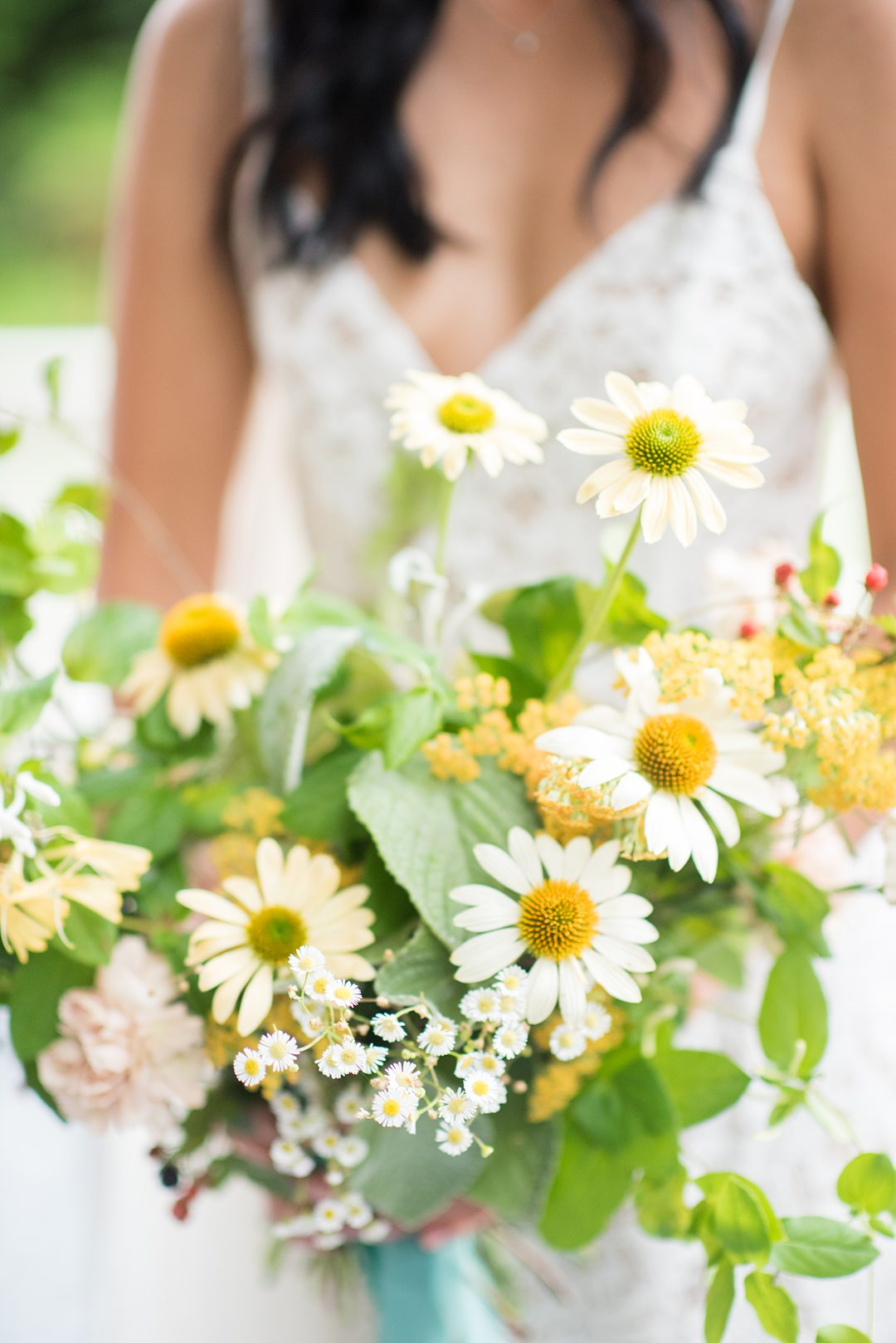 A wildflower bridal bouquet with berries, daisies and vines photographed by Mikkel Paige Photography and created by Mood Fleuriste. The couple eloped when COVID-19 changed their original plan. #mikkelpaige #wildflowerbouquet