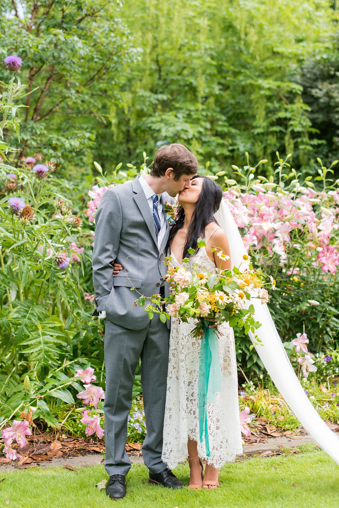 The bride and groom kiss amongst flowers in the park after their small outdoor ceremony. Wedding pictures by Mikkel Paige Photography. #mikkelpaige #raleighwedding #raleighNC #smallwedding