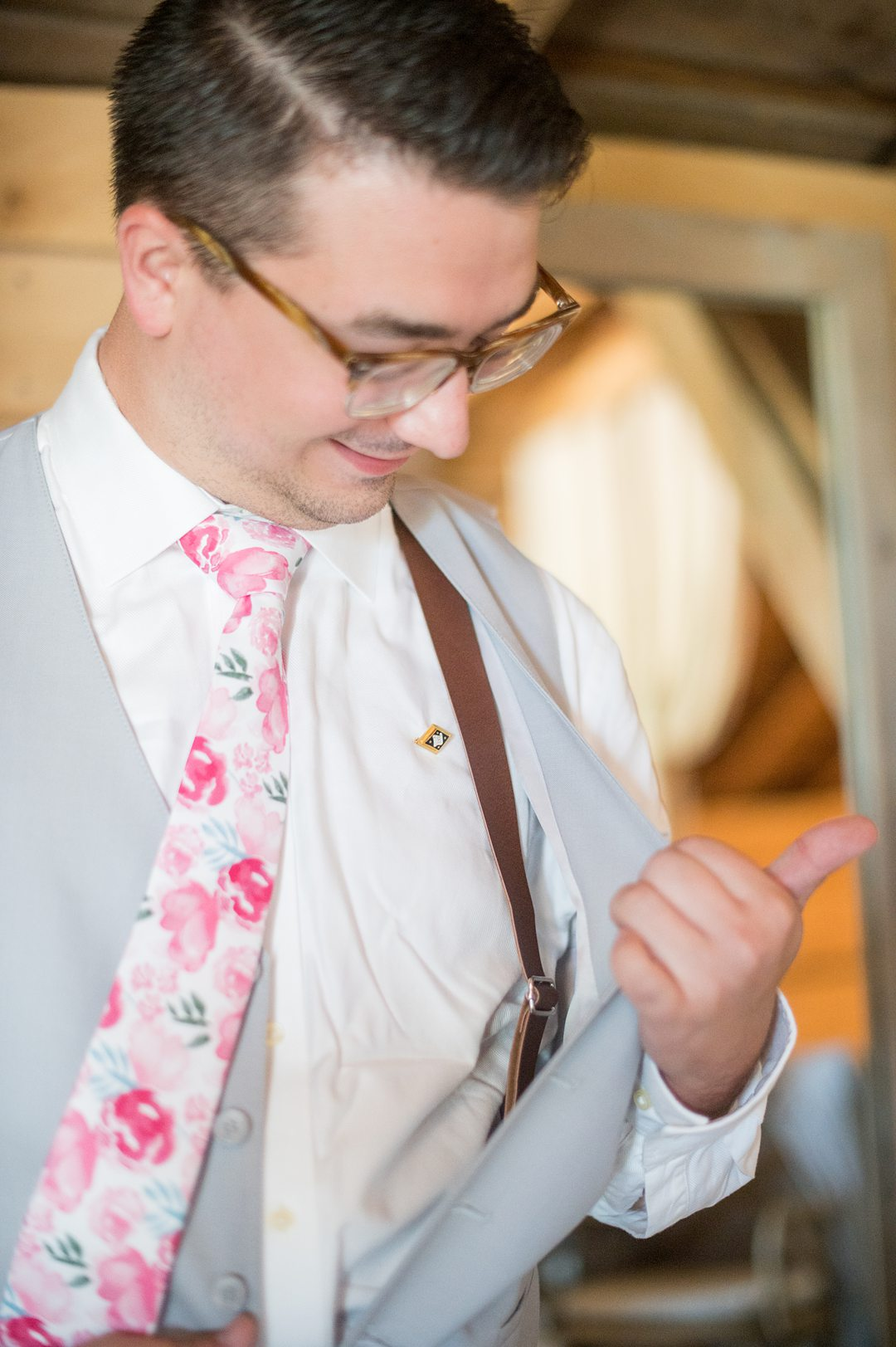 Groom in a grey suit with a pink floral tie and pocket square, and brown leather suspenders, for a small wedding in Charlottesville, VA during COVID. Photos by Mikkel Paige Photography.
