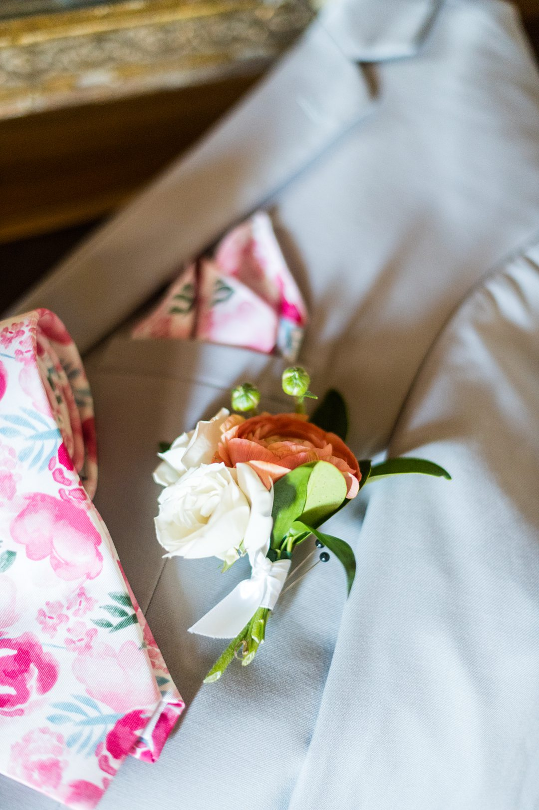 A ranunculus and spray rose boutonniere and pink floral tie and pocket square, for a small wedding in Charlottesville, VA during COVID. Photos by Mikkel Paige Photography.