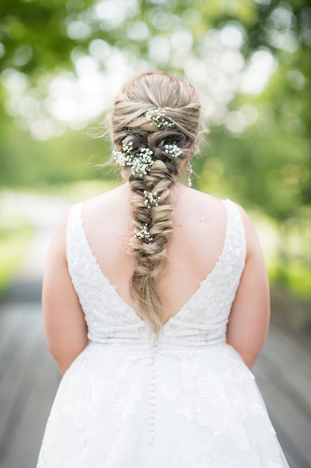 The bride had baby's breath in her fish tail style braid for her wedding day look. Photos by Mikkel Paige Photography. #mikkelpaige #mountaidafarm #charlottesvillewedding