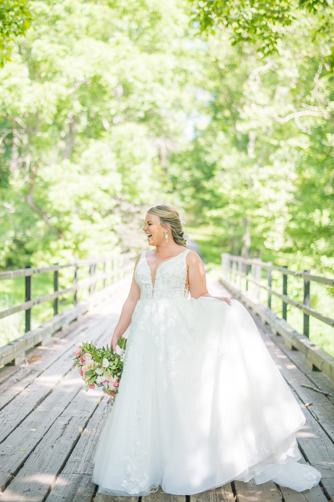 Bride in a tulle skirt and deep v gown with a summer bouquet with peonies by Mikkel Paige Photography. The wedding was at The Lodge at Mount Ida Farm in Charlottesville, VA.