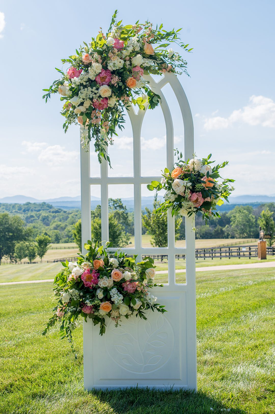 Small wedding ceremony details, in windows that were custom made and decorated with summer flowers. Photos by Mikkel Paige Photography at The Lodge at Mount Ida Farm in Charlottesville, VA. Planning by Mary Elizabeth Events. #mikkelpaige #Charlottesvillewedding #picturesqueceremony