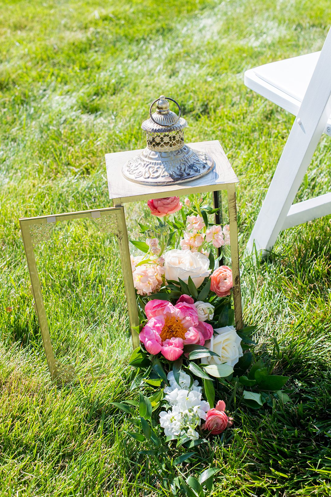 Small wedding ceremony flowers spilling out of a lantern.