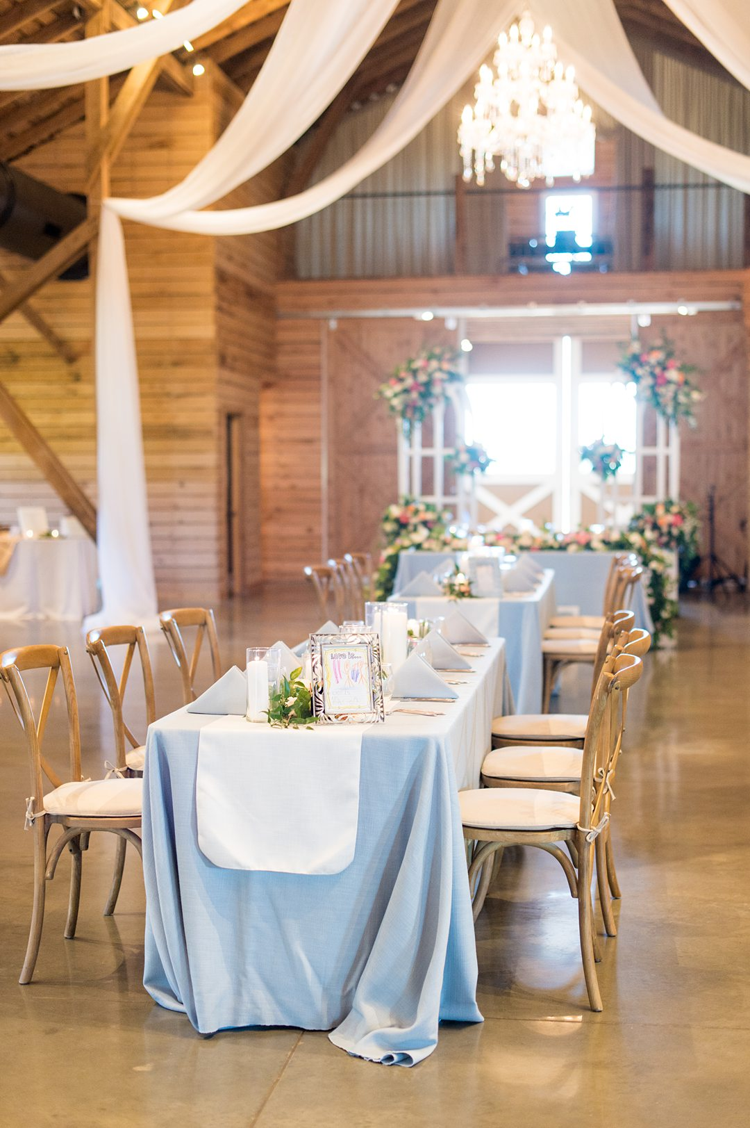 Blue linens with white runners and flowers lined the tables at a small wedding reception at The Lodge at Mount Ida Farm in Charlottesville, VA. Photos by Mikkel Paige Photography. #mikkelpaige #charlottesvillewedding #CharlottesvilleVA #MountaIdaFarm #weddingreception