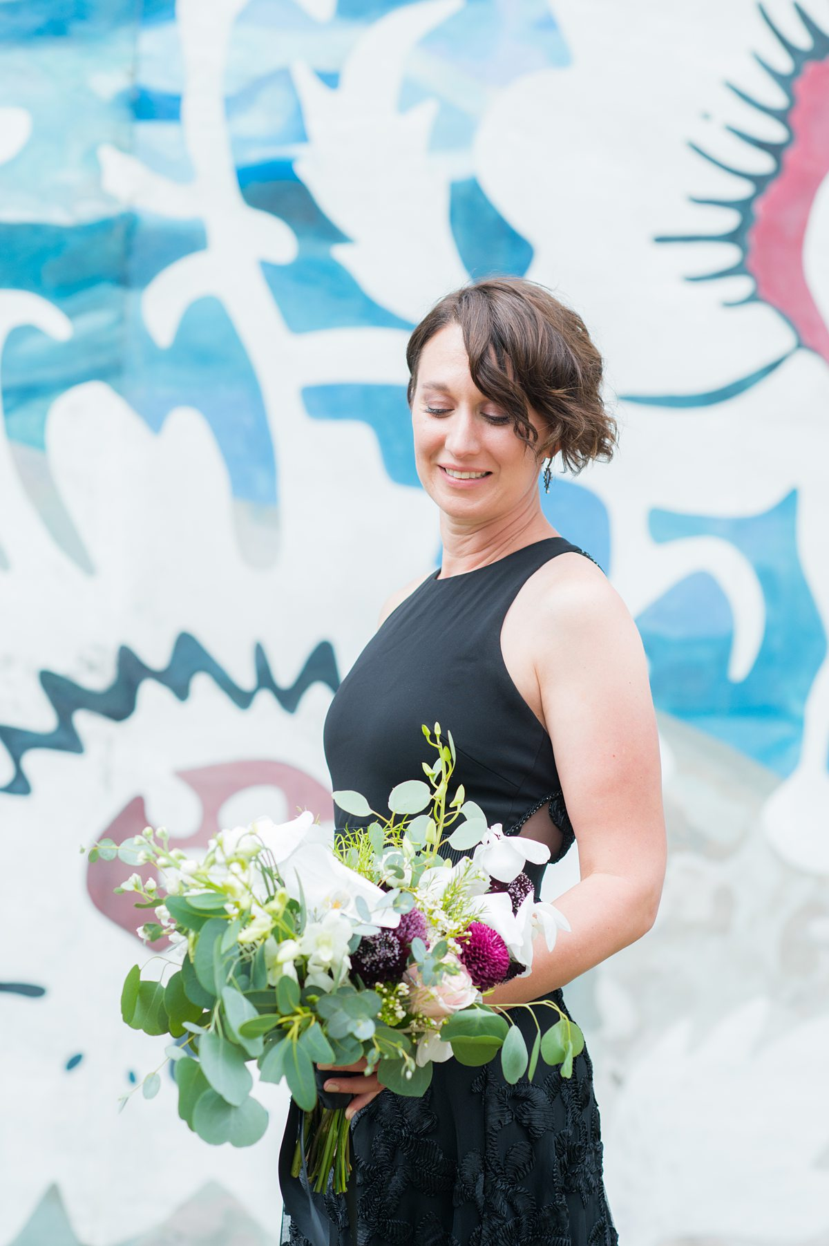 Bride in a black gown with colorful mural behind her.