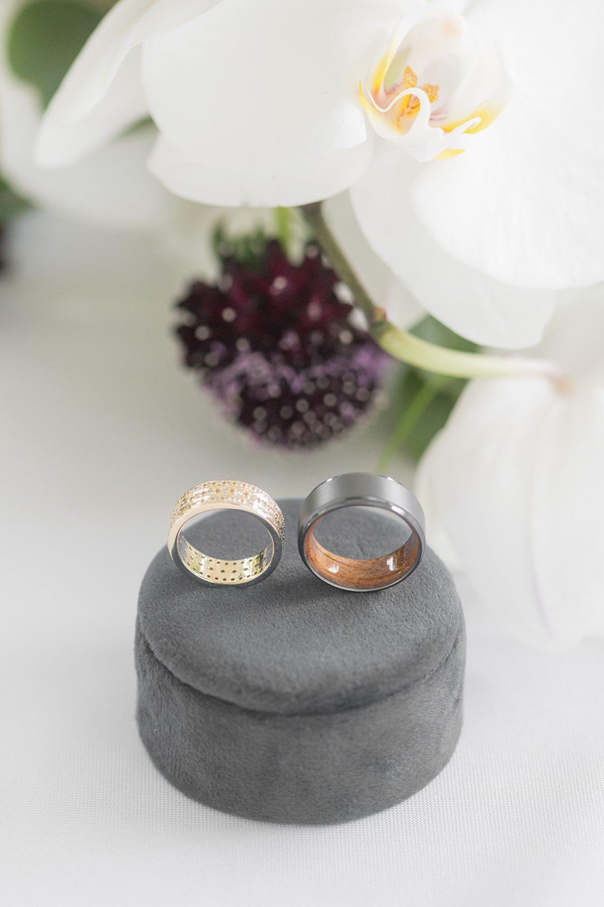Wedding rings on a grey velvet round ring box.
