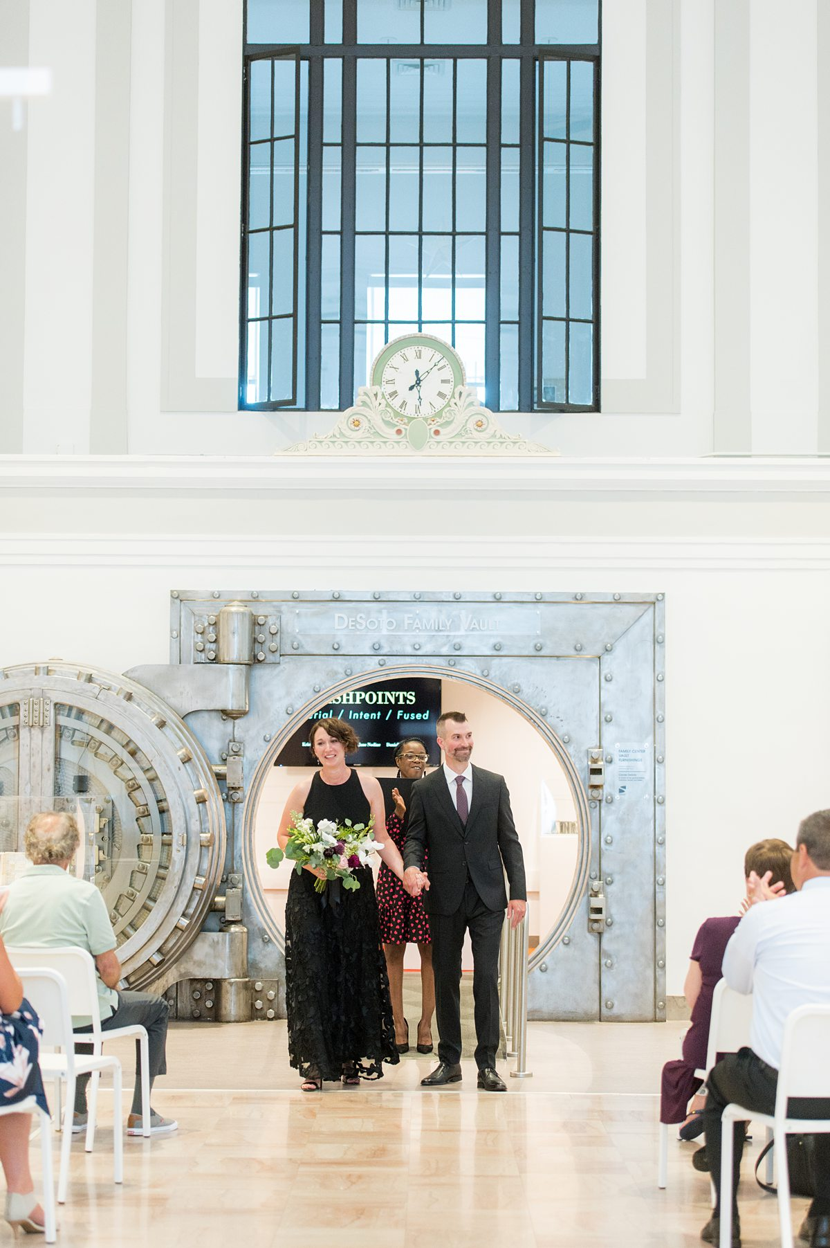 Wedding ceremony at an art museum, in front of an old safe.