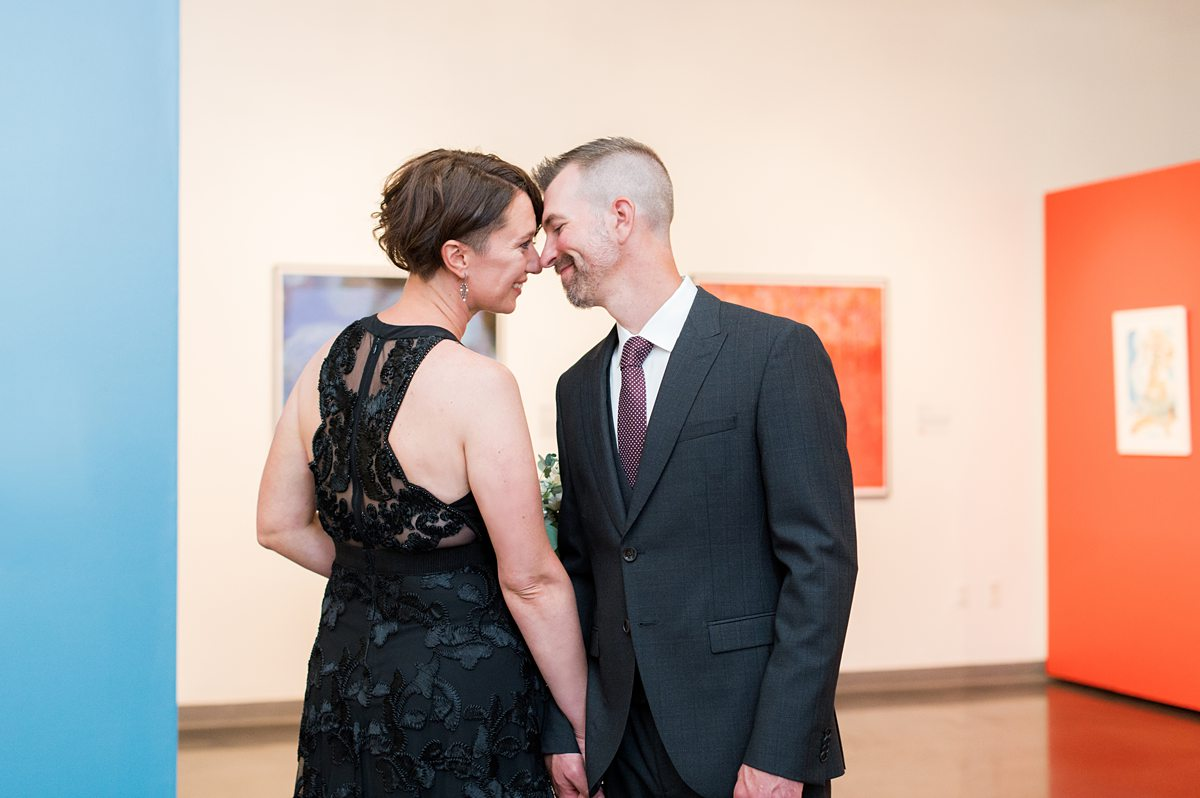Bride and groom in formal wear at an art museum.