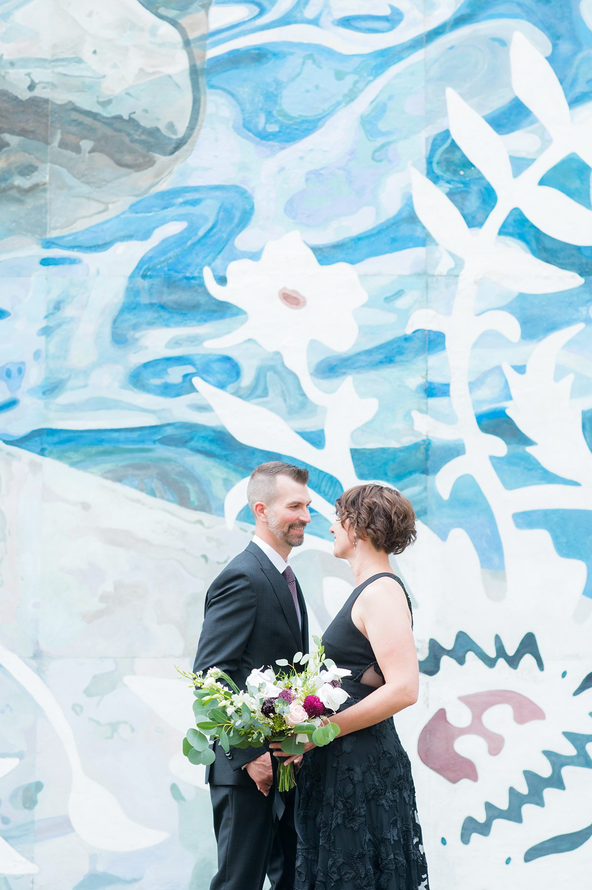 Bride and groom in front of a colorful mural.