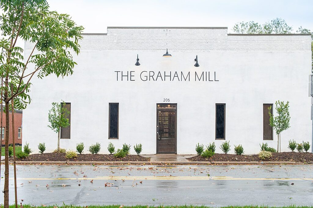"Front of a building painted in white with ""The Grand Mill"" painted in black letters on top."