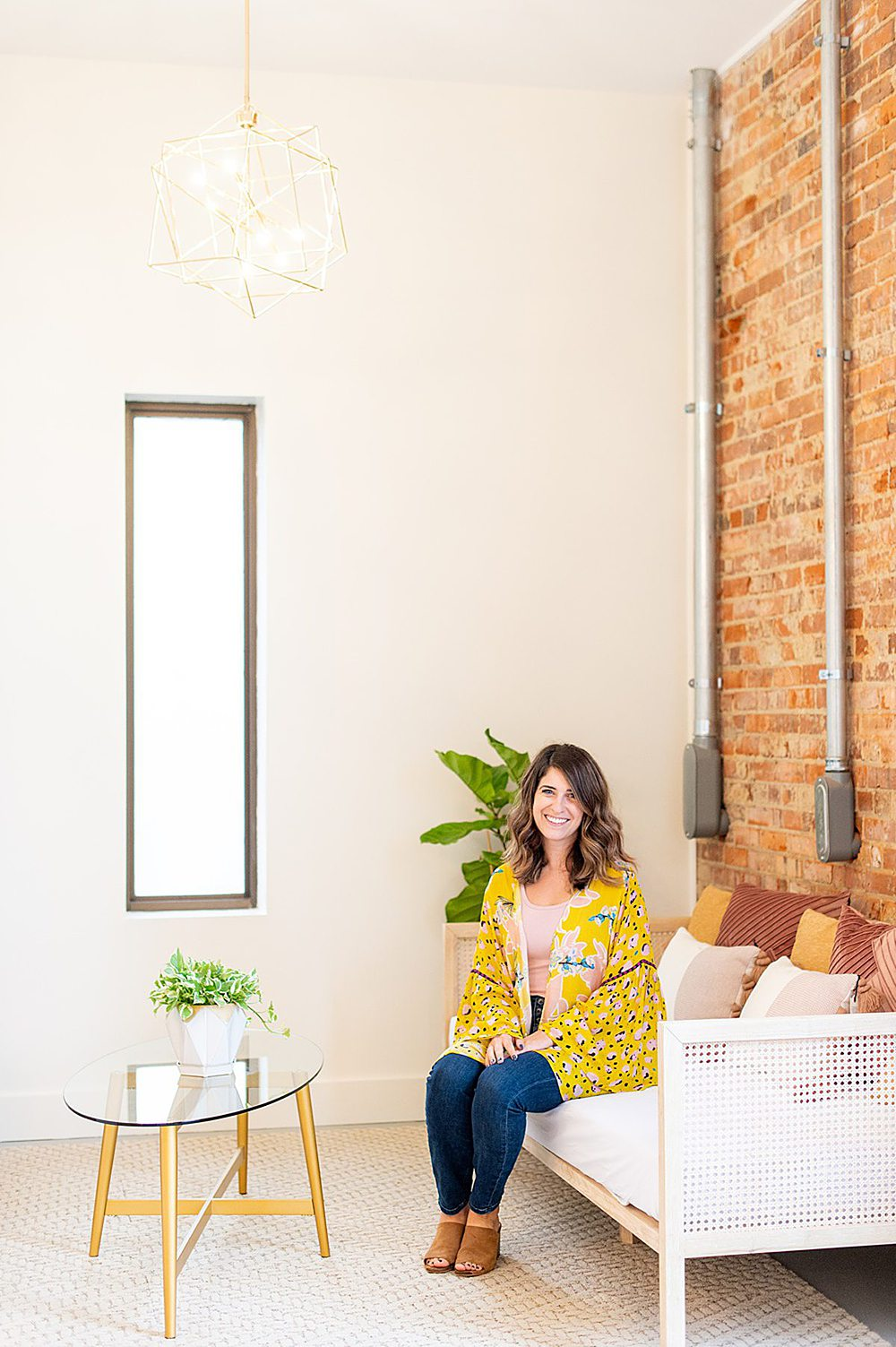 A woman in pink and yellow on a couch with a brick wall behind her and glass coffee table in front of her at The Graham Mill.