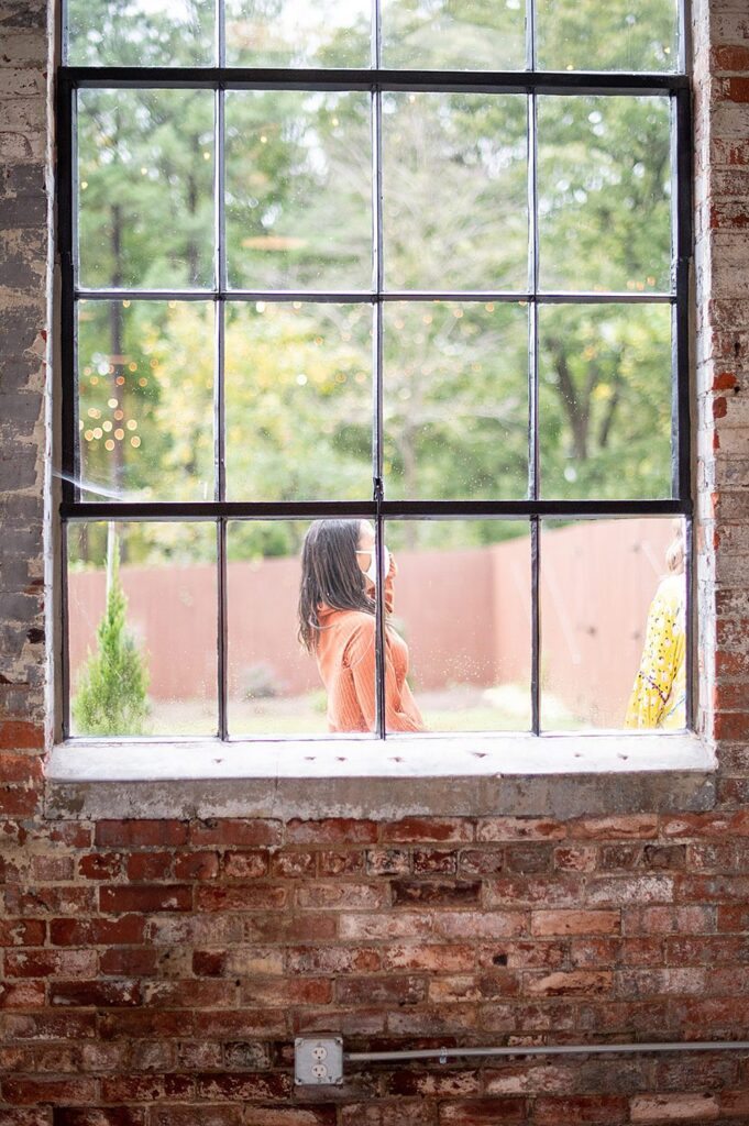 A woman in an orange shirt seen through the window of The Graham Mill in NC.