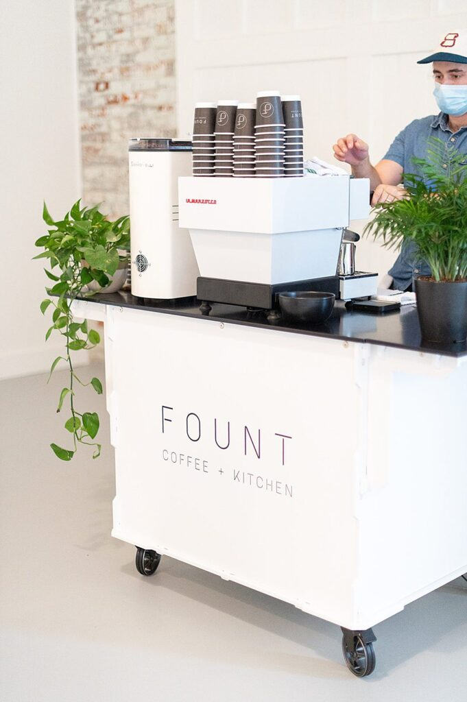 White coffee cart that says Fount Coffee + Kitchen at an event at The Graham Mill in NC.