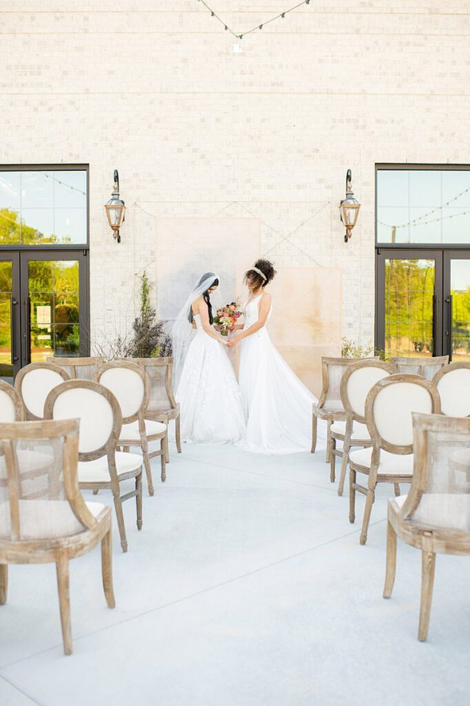 Two brides at an outdoor ceremony at The Maxwell, a modern wedding venue.