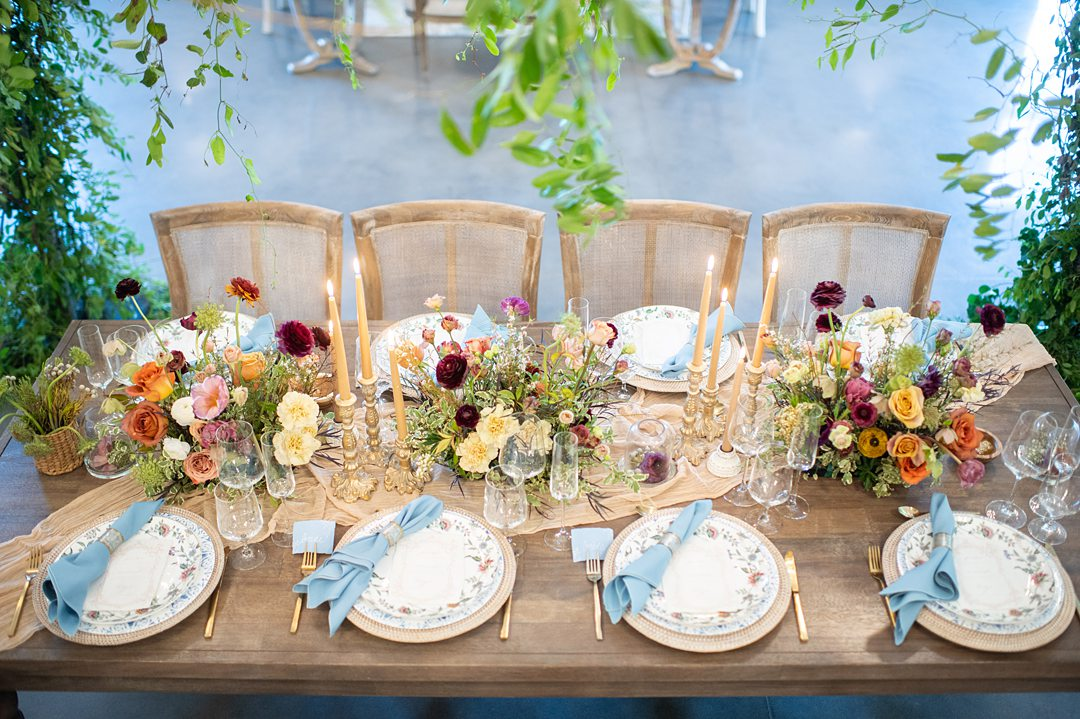 Wooden table with chairs, and plates with blue napkins under a greenery canopy at The Maxwell in NC.