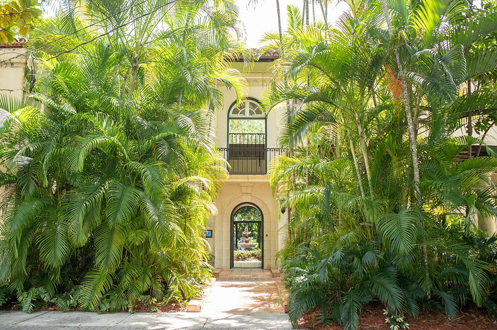 Front entrance archway and second floor Juliet balcony framed by palm trees, at Villa Woodbine. This historic home is a wedding venue in Miami, FL. Picture by Mikkel Paige Photography.